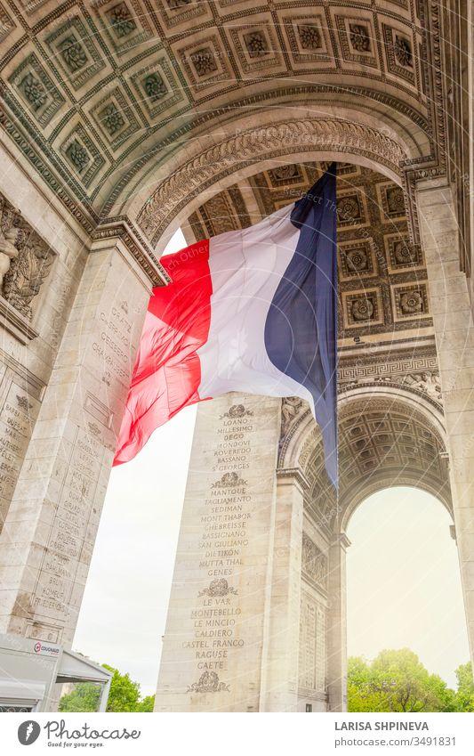 Blick auf den Arc de Triomp mit der im Wind wehenden französischen Flagge auf dem Place de Gaulle in Paris, Frankreich Bogen triumphieren Fahne Denkmal Europa