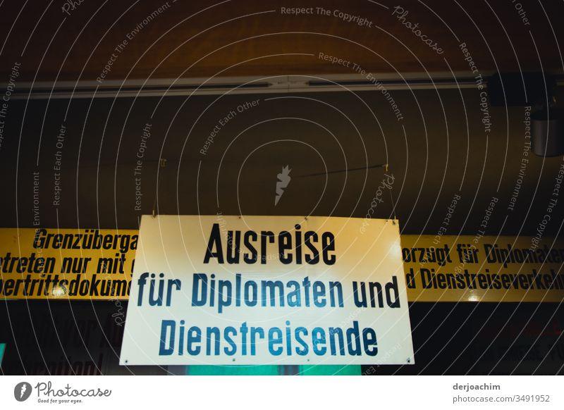 Ein Großes in weiß gehaltenes  Hinweis - Schild / Ausreise für Diplomaten und Diestreisende / Grenzübergang DDR - Deutschland Berlin. schild Architektur modern