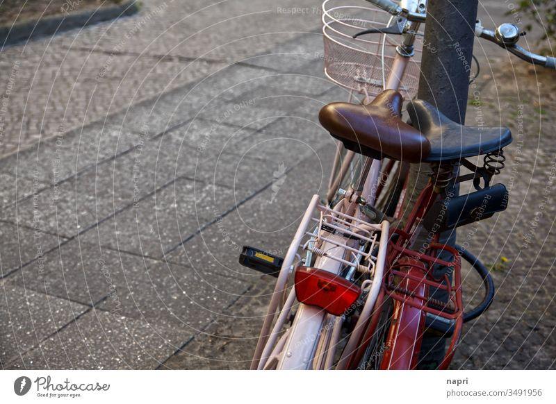 Zwei Fahrräder stehen eng beieinander an einen Laternenmast gelehnt. Fahrrad zwei Fahrradfahren Ausflug anlehnen Zusammensein Zweisamkeit Vintage retro alt