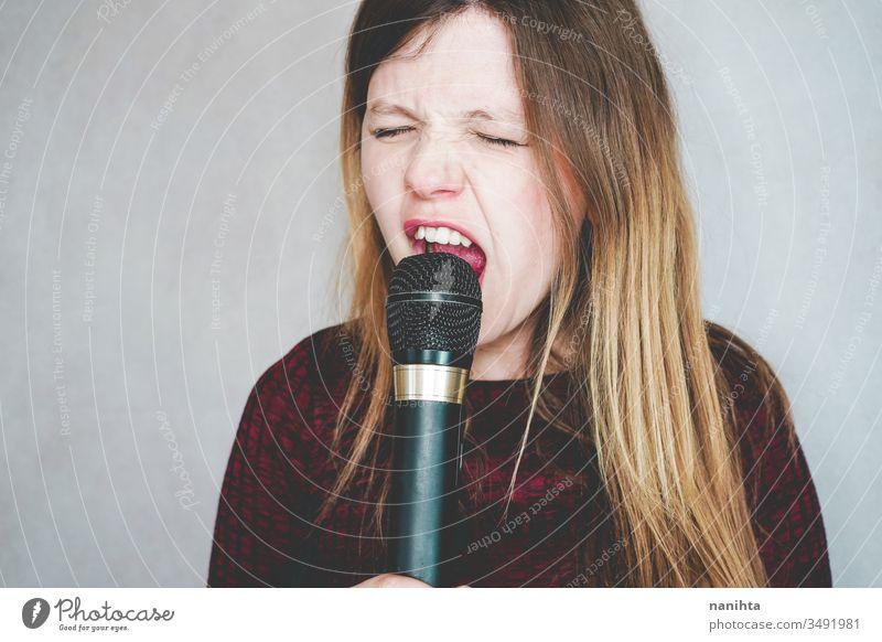 Junge Frau singt mit einem Mikrofon singen Gesang laut Technologie Klang Kunst Künstler Konzept Freizeit Aktivität aktiv blond lässig wirklich Menschen