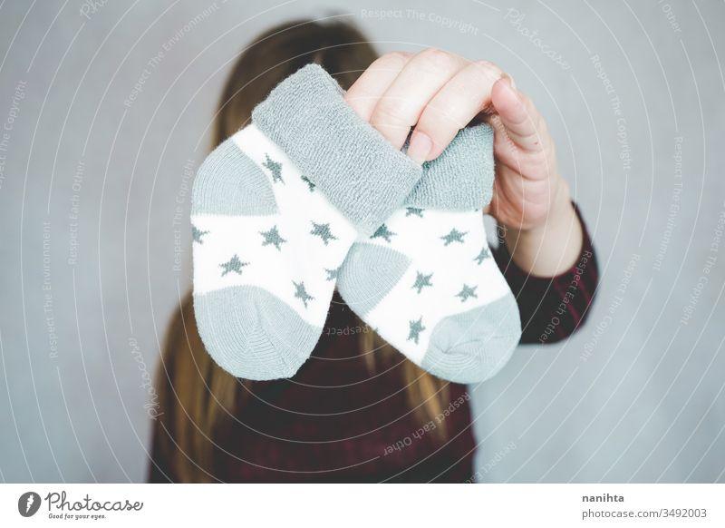 Junge schwangere Frau hält Babysocken Schwangerschaft Socken Mama Glück Fröhlichkeit erwartend erwartungsvoll Mutterschaft Liebe lieblich weich schön Schönheit