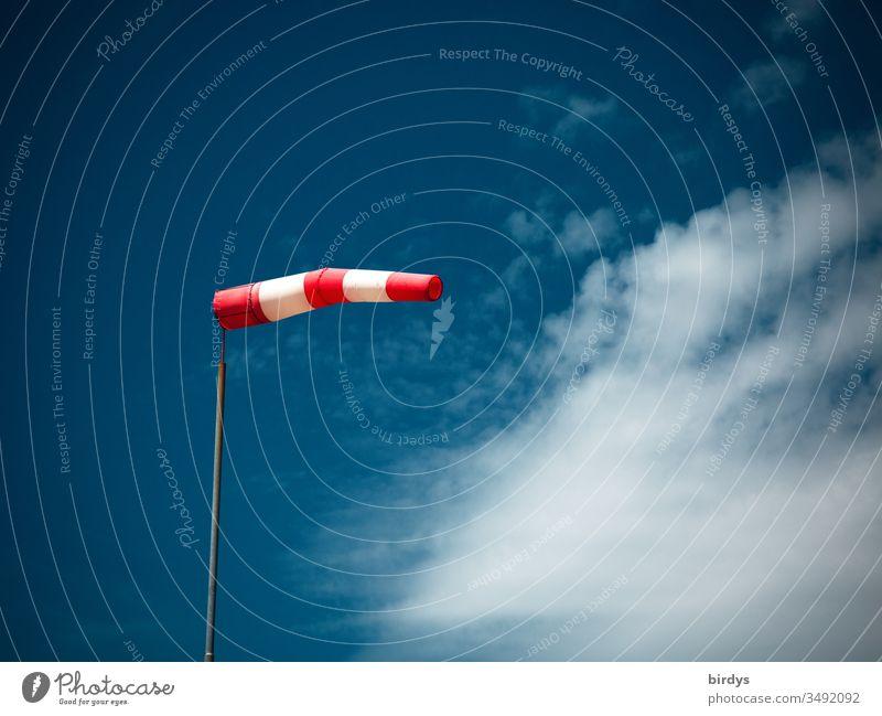aufgeblähter Windsack bei starkem Wind vor blauem Himmel und Wolken Windrichtung rot-weiß Richtungsanzeiger wehen Schönes Wetter Menschenleer Farbfoto