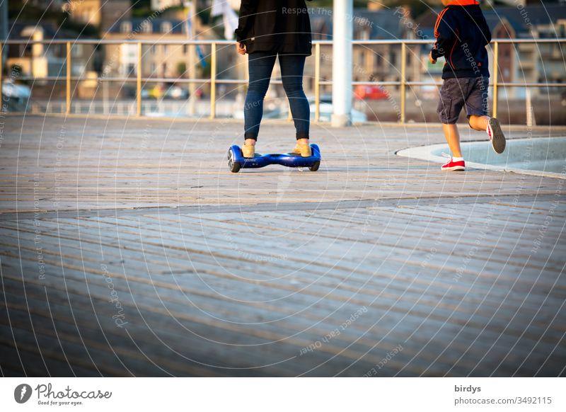 Erwachsene fährt auf einem Hoverboard, Kind läuft , rennt nebenher Bewegung elektrisch Fortbewegung Jugendliche laufen fahren rennen Mensch Beine