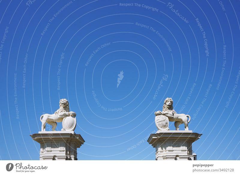 zwei Löwen mit Schild auf Steinsäulen vor blauem Himmel Außenaufnahme Menschenleer Granit Naturstein Mähne Tier Tierporträt Wappen Farbfoto Säulen Tiergesicht