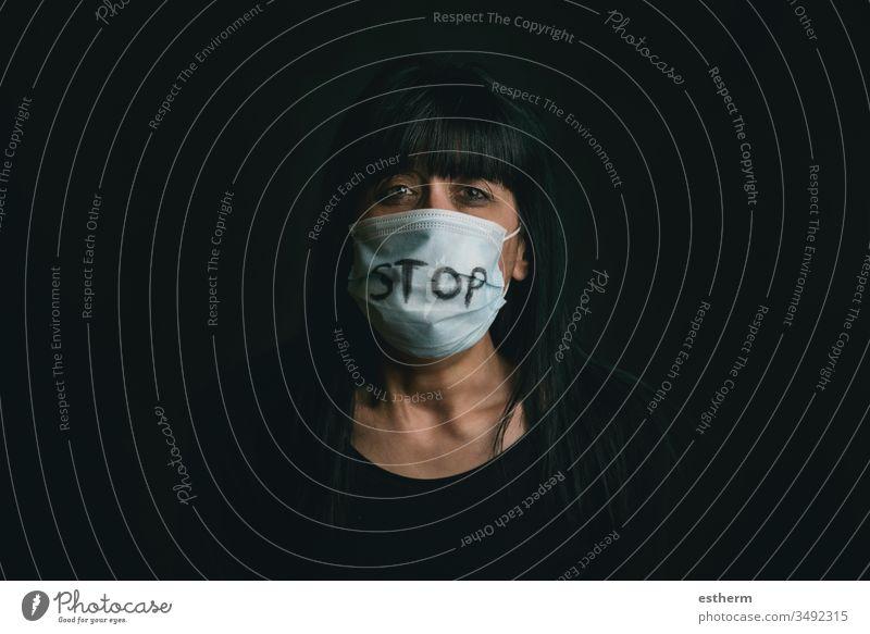 Stop Violence,verängstigte Frau mit medizinischer Maske für Coronavirus-Opfer häuslicher Gewalt Virus Seuche Pandemie Quarantäne Angst Aggression Gefahr