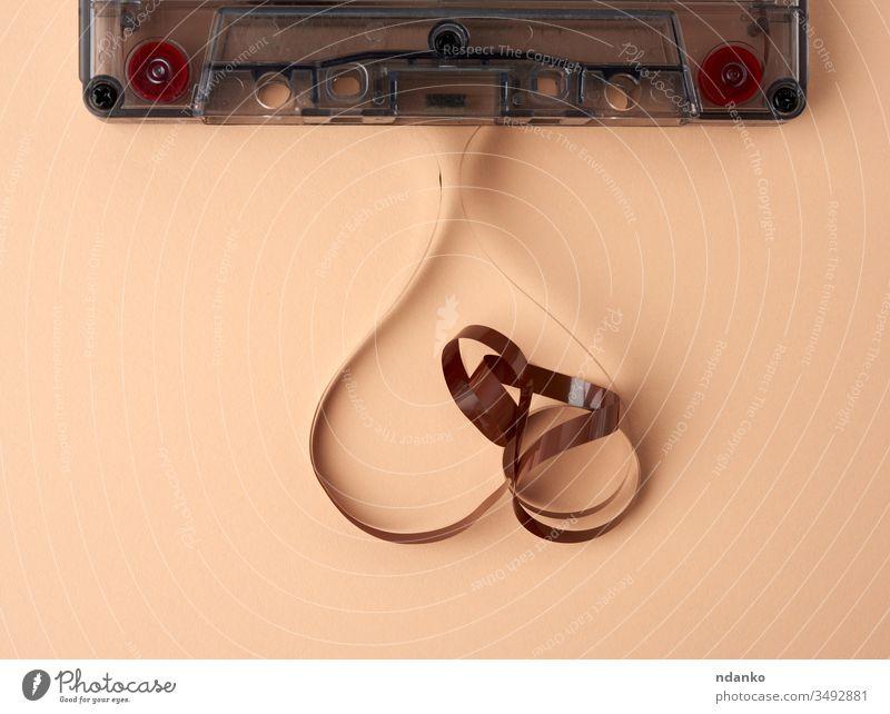 Kassette mit einem braunen Magnetband auf beigem Hintergrund Technik & Technologie Achtziger Gerät Aufzeichnen alt Klebeband retro altehrwürdig Musik magnetisch