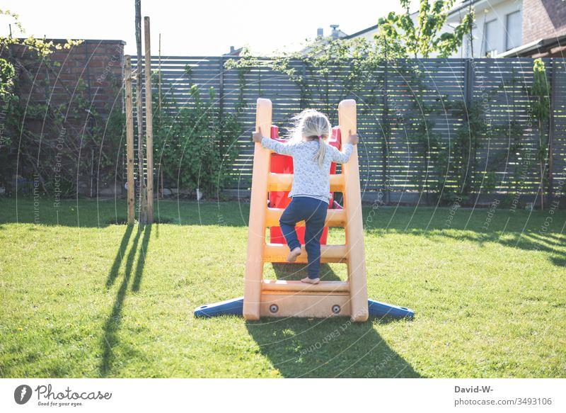 Kind klettert im Garten die Rutsche hoch spielen rutschen zu Hause Mädchen Spaß Freude Fröhlichkeit Lebensfreude