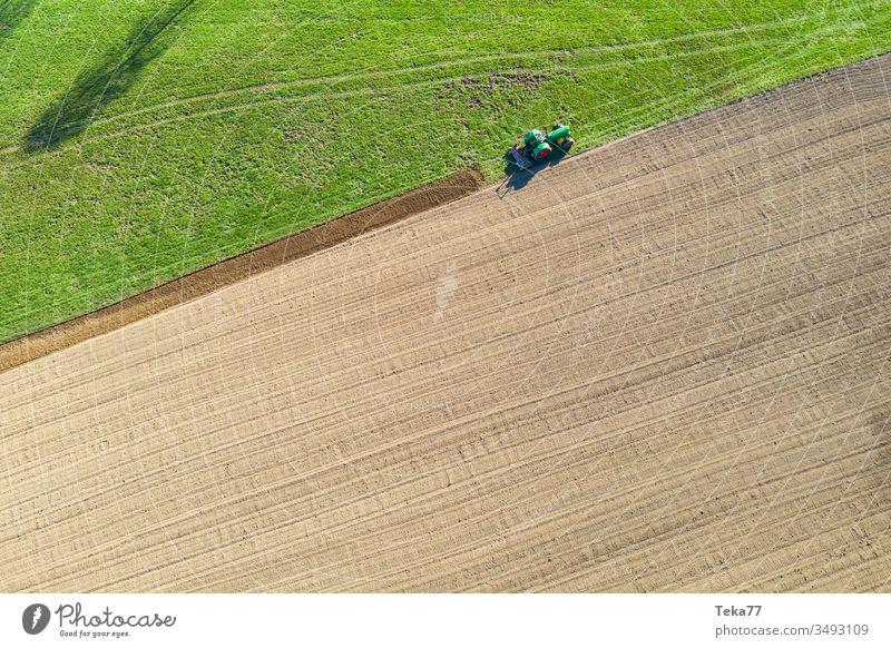 Traktor gräbt ein Feld von oben Traktor von oben historischer Traktor grüner Traktor Traktor auf einem Feld landwirtschaftlich Landwirtschaftlicher Weg