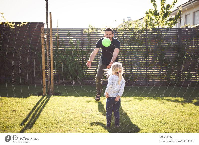 Kind und Vater spielen im Garten mit einem Ball werfen und fangen Mädchen Mann Tochter Spielen beschäftigen spass lachen Freude fliegen Schatten Sonnenlicht