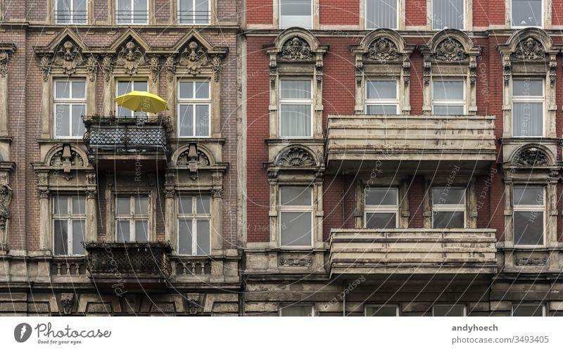 Der gelbe Sonnenschirm auf dem Balkon des alten Hauses antik Antiquität Appartement Bogen Architektur Balkone Berlin Backsteinwand Gebäude Gebäudeaußenseite