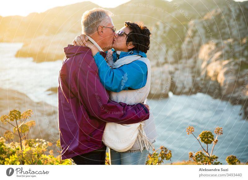 Liebevolles, reifes Paar, das reist, auf der Spitze eines Felsens steht und forscht. Aktiver Mann und aktive Frau, die sich umarmen und küssen, glücklich lächelnd. Panoramablick auf Berge und Meer bei Sonnenuntergang. Norwegen, Lindesnes