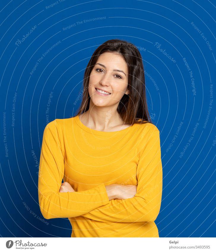 Brünette junge Frau trägt ein gelbes T-Shirt Mädchen Person blau Lächeln entspannt in die Kamera schauen Lachen Freude froh freudig Selbstvertrauen