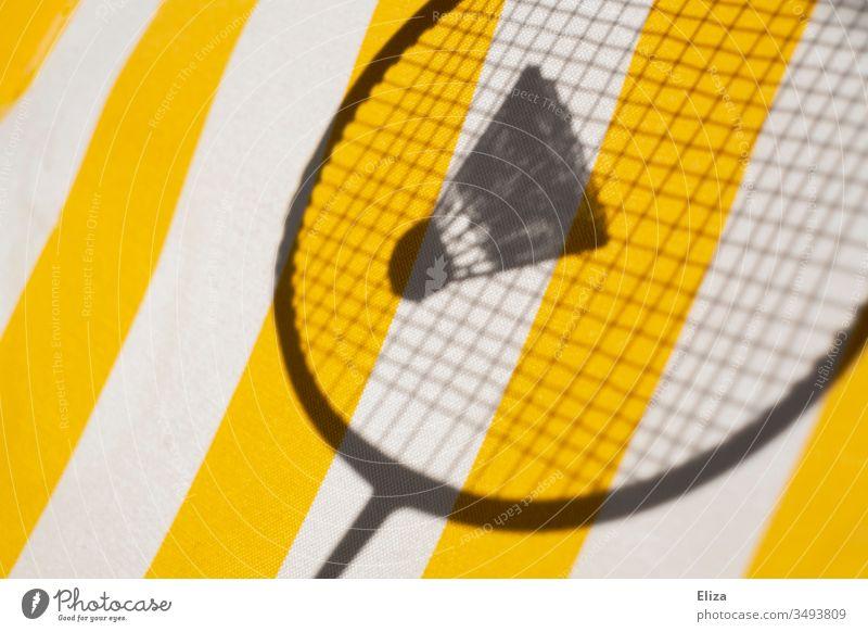 Der Schatten eines Federballschlägers mit einem Federball vor gestreiftem gelben Hintergrund; Badminton Badmmintonschläger Sport Ballsport Freizeit & Hobby