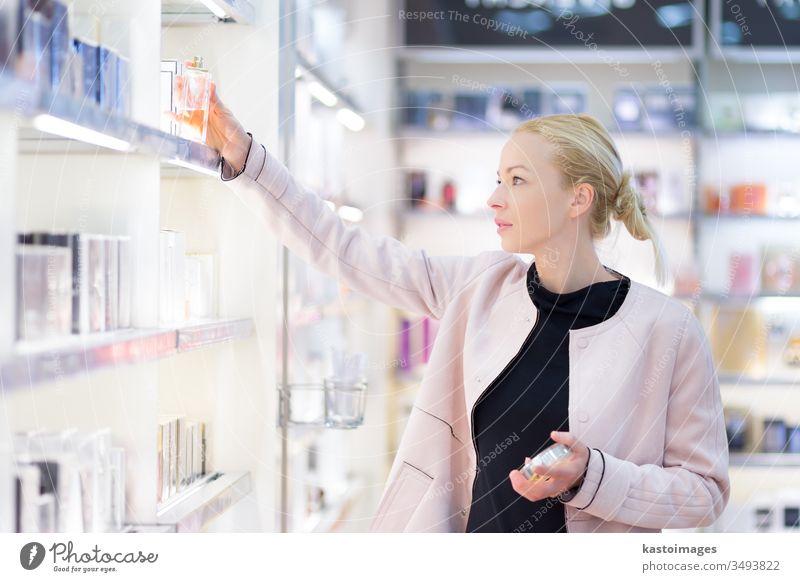 Schöne Frau beim Einkaufen im Schönheitssalon. Werkstatt Käufer Kosmetik Markt Drogerie Duft Tester Duftwasser Wittern Laden Erwachsener Regal lässig Boutique