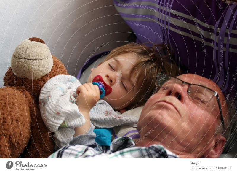Opa, Enkel und der Teddy machen gemeinsam Mittagsschlaf Senior Mann Kind Kleinkind Teddybär schlafen ruhen miteinander geschlossene Augen Brille Schnuller