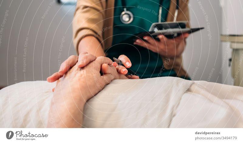 Ärztin tröstet ältere Patientin unkenntlich alt Hände Arzt Coronavirus covid-19 Tod medizinisch beruhigen liebevoll Krankenhaus Senior Sterblichkeitsrate