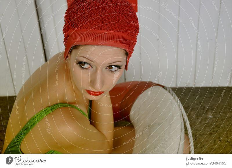 Das Mädchen mit der schönen roten Badekappe und dem grünem Badeanzug hockt in einem Rettungsring. Eine Sommerliebe. Frau Badebekleidung Badehaube Haut jung