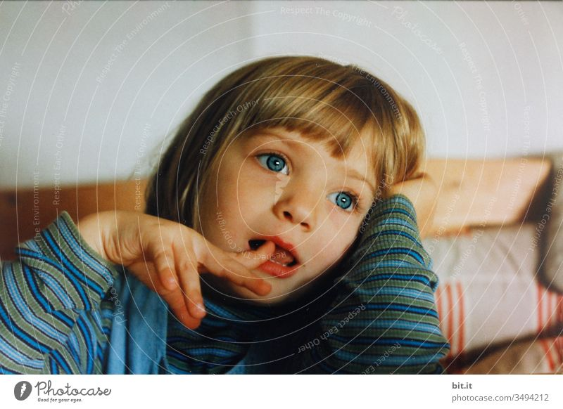 Kleines, süßes Mädchen im Ringelshirt, sitzt auf einer Holzbank am zuhause Tisch und träumt blauäugig in die Luft, dabei steckt sie den Zeigefinger in den offenen Mund.