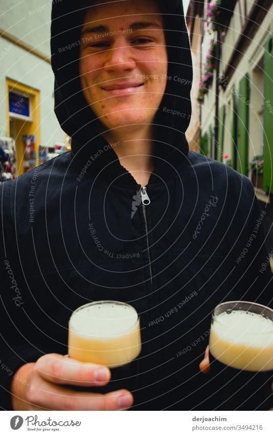 Junger Mann hält zwei Gläser mit dunklem  Bier auf der Straße  ( Rauchbier ) in der Hand und lächelt. Der Weiße Schaum  in den Gläsern ist gut an seiner dunklen Jacke zu erkennen.