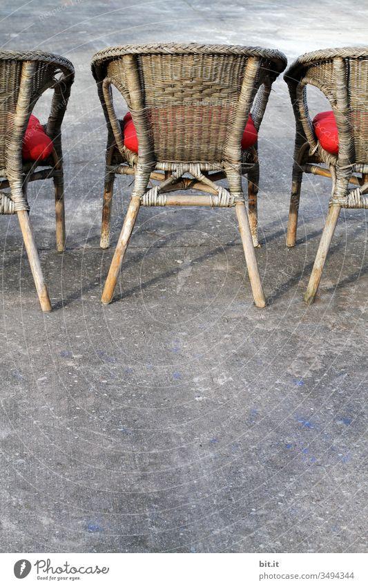 Dreiklang l Ein Ganzer und zwei Halbe. Stuhl Stühle Korbstuhl Kissen Sitzgelegenheit Asphalt Beton Möbel sitzen Sessel Polster Erholung warten trist Einsamkeit
