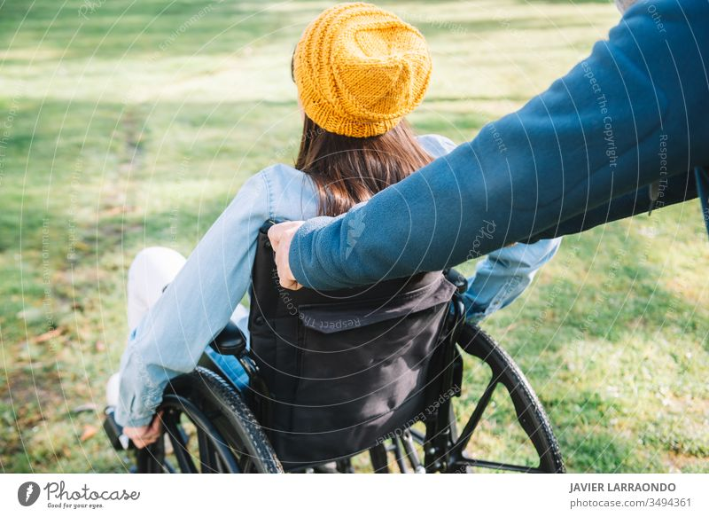 Freiwilliger schiebt den Rollstuhl eines jungen behinderten Mädchens in einem ga Zugänglichkeit Behinderung Frau Fröhlichkeit Optimismus Mobilität Behinderte