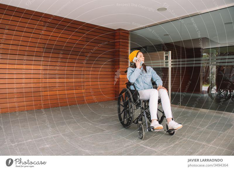 Behindertes Mädchen im Rollstuhl, das mit ihrem Handy telefoniert deaktivieren jung Frau Smartphone Technik & Technologie Mitteilung verletzt Lifestyle