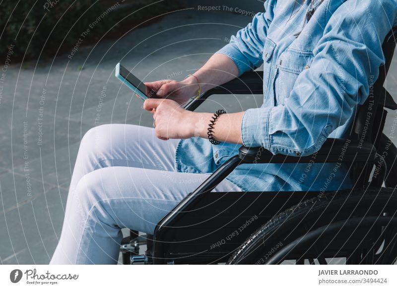 Behindertes Mädchen im Rollstuhl bei der Benutzung ihres Mobiltelefons Mitteilung deaktiviert Smartphone lässig Lifestyle Selbstständigkeit
