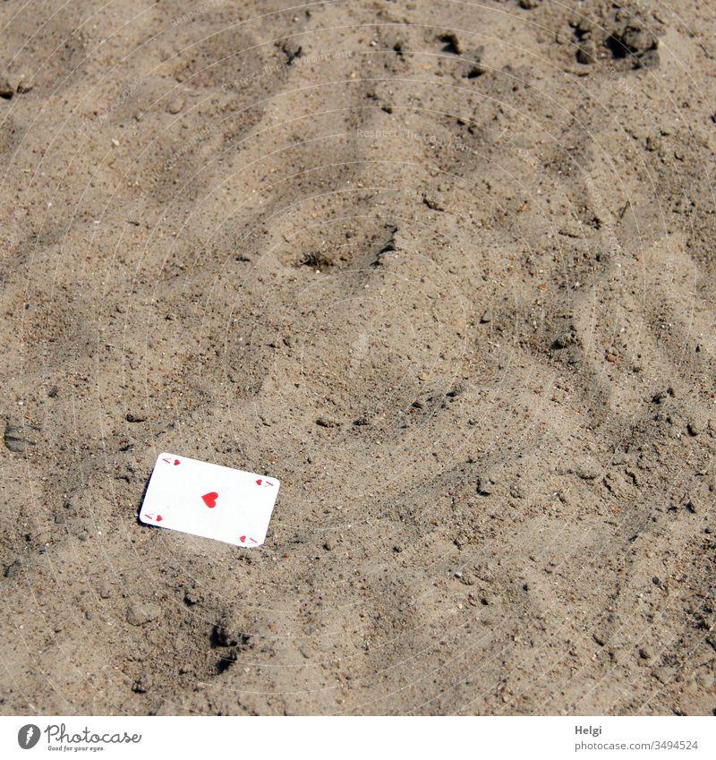 aus dem Ärmel gefallen ... ;-)    eine Spielkarte Herz-As liegt im Sand Glücksspiel verloren liegen Karte Kartenspiel Freizeit Hobby Spielsucht Freude Hoffnung