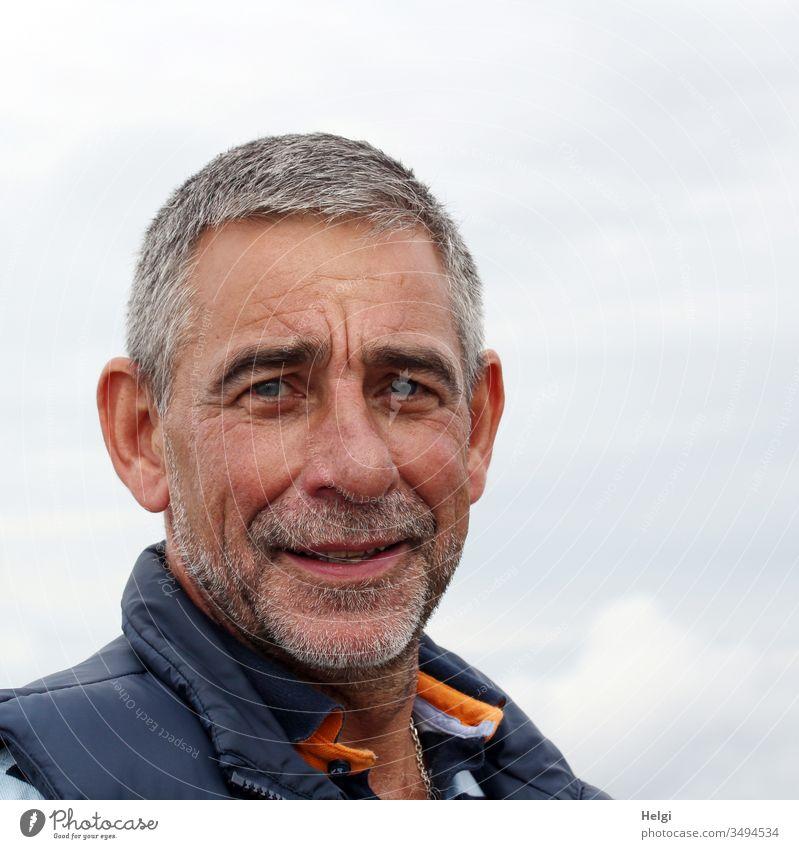 Porträt eines Senioren  mit kurzen grauen Haaren und Dreitagebart vor blaugrauem Himmel Mensch Mann grauhaarig kurzhaarig Bart Lächeln freundlich 1 Erwachsene
