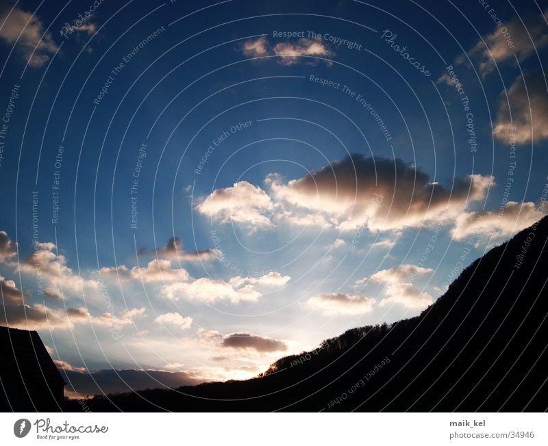 Sonne versinkt hinter Bergen Wolken Sonnenstrahlen Stimmung Licht Himmel Abend Natur Lampe Beleuchtung