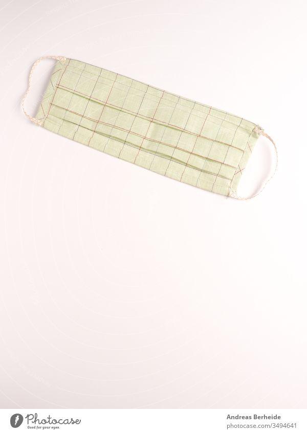 Nahaufnahme eines selbstgemachten Mundschutzes auf hellem Hintergrund Schutz schützend Gesichtsschutz Grippe-Virus Verunreinigung Atemwegsinfektion