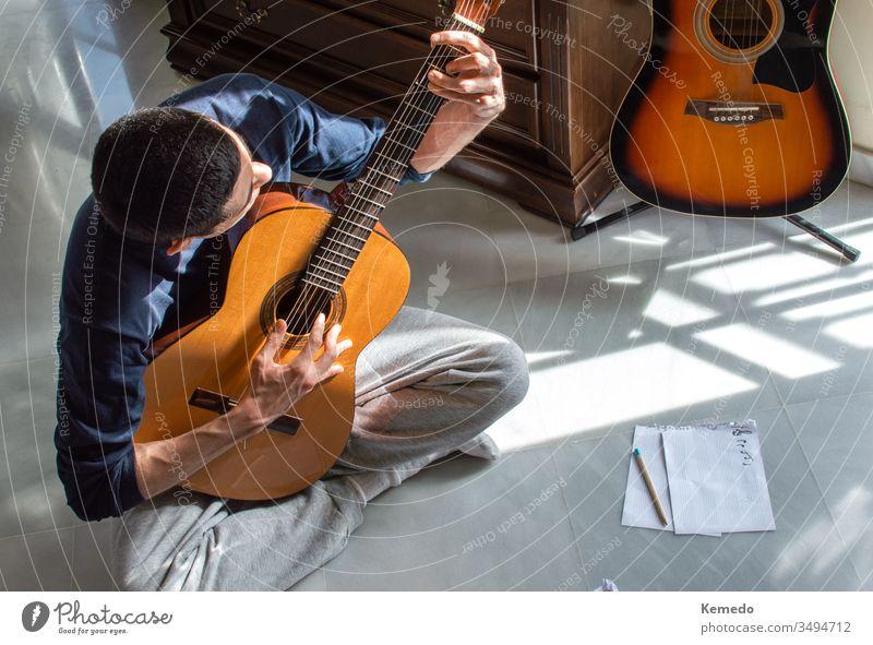Mann, der an einem sonnigen Tag zu Hause in der Nähe eines hellen Fensters Gitarre spielt und Musik komponiert. Gelegenheitsmusiker, der auf dem Boden sitzt und Gitarre spielt.
