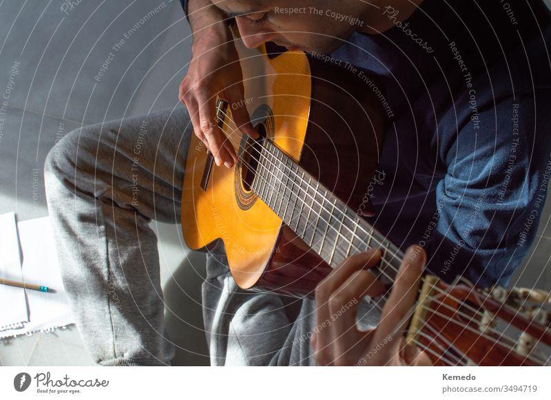 Draufsicht auf einen jungen Mann, der zu Hause Gitarre spielt und Musik komponiert. Lässiger Mann, der auf dem Boden sitzt und Gitarre lernt. spielen lernen