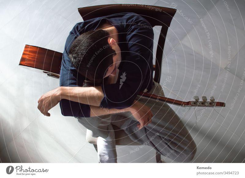 Gelangweilte und uninspirierte junge Leute machen eine Pause vom Gitarrenspiel. Draufsicht auf einen Mann, der sich mit einer Gitarre ausruht. Konzept des Mangels an Inspiration oder Motivation.