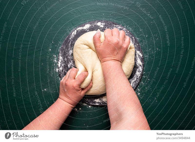 Kneten von Pizzateig auf grünem Tisch. Teig kneten zu Hause obere Ansicht backen Bäckerei Brot backen farbenfroh Essen zubereiten Teigwaren flache Verlegung