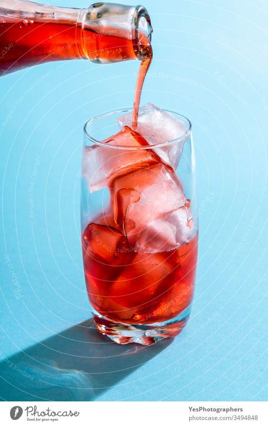 Übergießen mit Erdbeersirup in einem Glas Wasser. Getränk blau hell Nahaufnahme Cocktail Erfrischungsgetränk farbenfroh Textfreiraum kristallklar lecker Entzug
