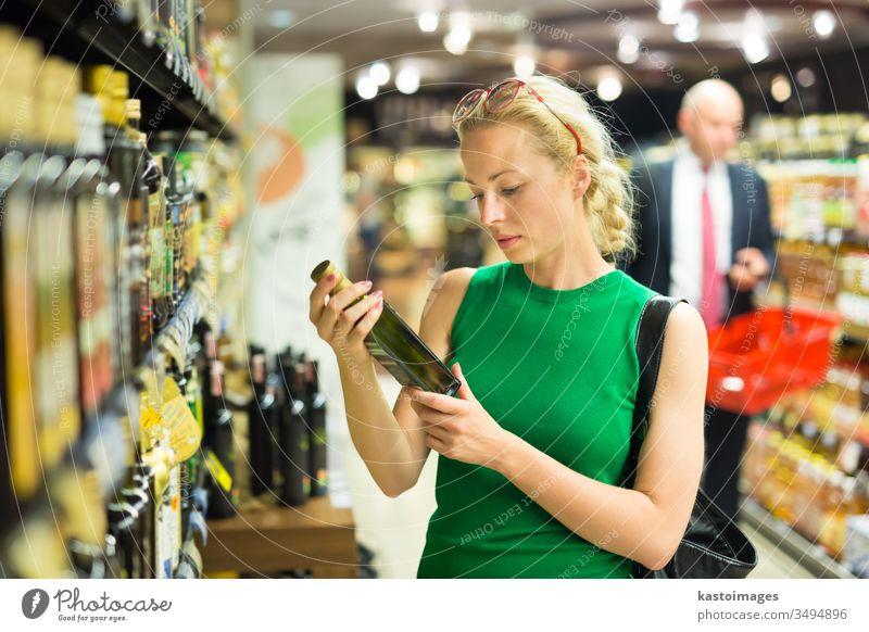 Frau kauft Lebensmittel im Supermarkt ein. Lebensmittelgeschäft Laden Kunde Markt Verbraucher Korb Menschen jung Werkstatt Person kaufen Gewerbe Erwachsener