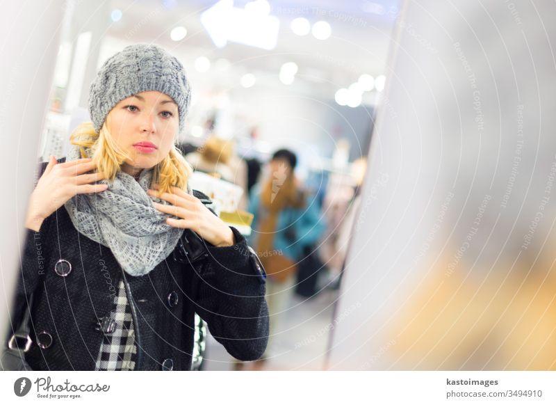 Schöne Frau beim Einkaufen im Bekleidungsgeschäft. Laden Sale Kleidung Käufer Kunde Mädchen Verbraucher Erwachsener jung schön Mode Kaufhof Einzelhandel