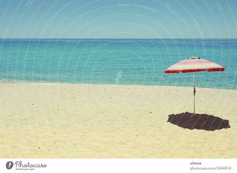 leerer Sandstrand mit einem Sonnenschirm vor blauem Meer bei Sonnenschein Strand Fernweh Menschenleer Wasser verwaist Sommer Ferien & Urlaub & Reisen Küste