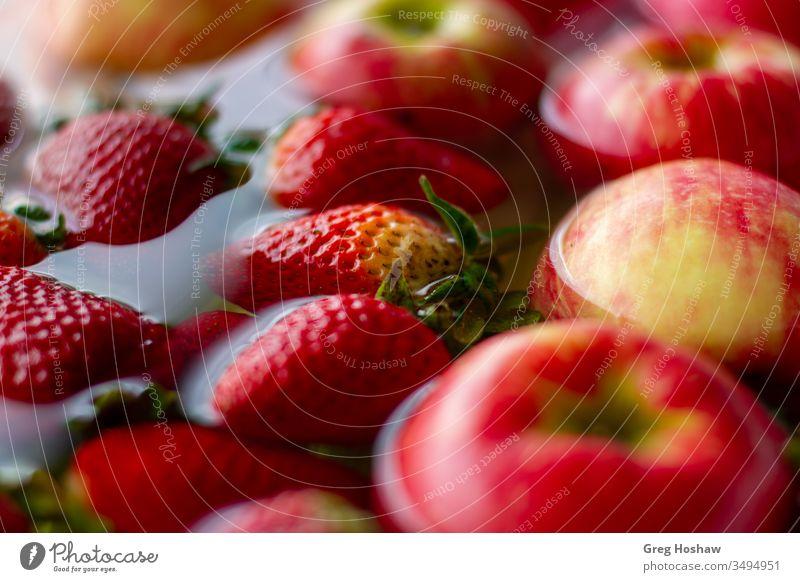 Nahaufnahme von frischen Bio-Erdbeeren und Äpfeln, die im Wasser schwimmen Apfel organisch Frucht Bioprodukte Farbfoto Gemüse Gesundheit Veganer