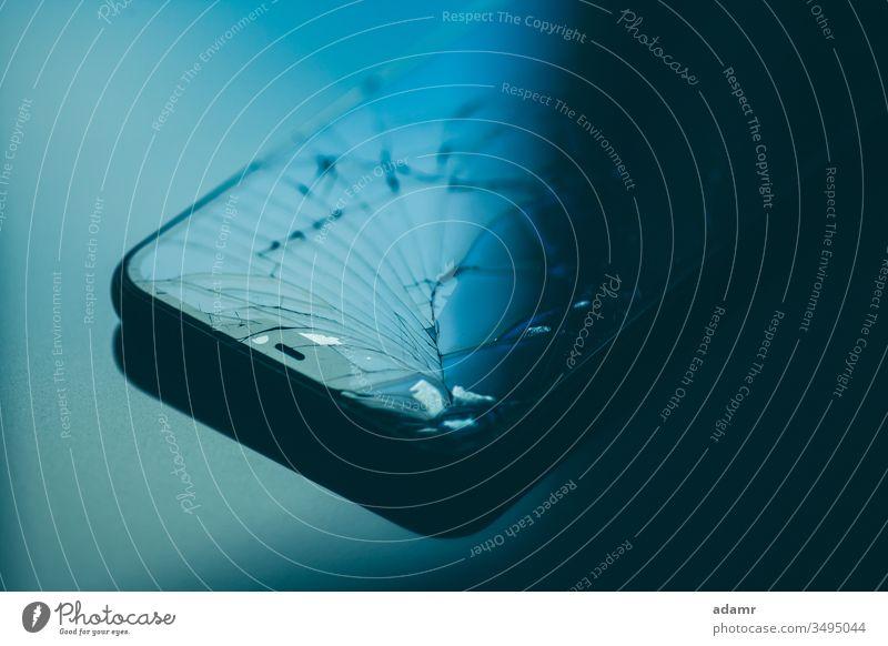 Smartphone mit kaputtem Bildschirm auf schwarzem Desktop Mobile Telefon Glas Zelle gebrochen Technik & Technologie Gerät Funktelefon Apparatur Anzeige