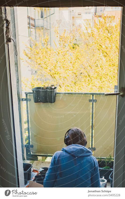 junge Frau sitzt mit Kopfhörern auf dem Balkon zum Hinterhof und pflanzt Blumen und Kräuter Ausblick Balconing Balkonbepflanzung Hobby Hoffnung Musik hören Saat