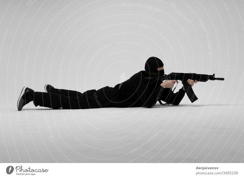 Mann in Maske mit Pistole auf weißem Hintergrund Aggression bewaffnet Sturmhaube schwarz Verbrechen Krimineller Gefahr böse Hand Beteiligung vereinzelt Mörderin