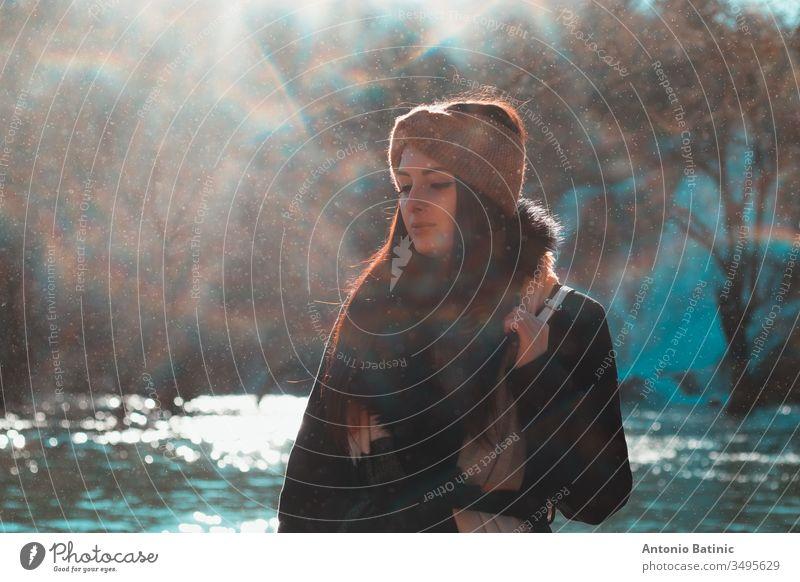 Attraktive Brünette in Winterkleidung und orangem Kopftuch, die an einem kalten Wintertag mit geschlossenen Augen posiert. Wassertropfen, die überall hinfliegen und einen Nebel, Nebel und Mini-Regenbögen erzeugen