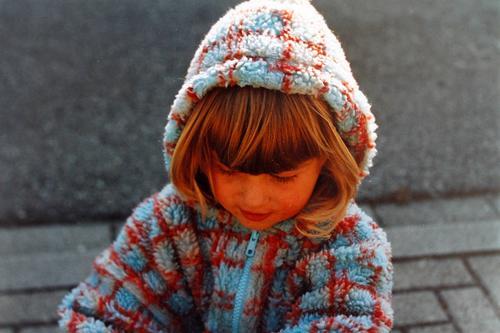 Mädchen in karierter Kuscheljacke aus Fleece, spielt, glücklich, unbekümmert und fröhlich, mit Kapuze auf dem Kopf, als Wetterschutz, im Herbst draussen auf der Straße.