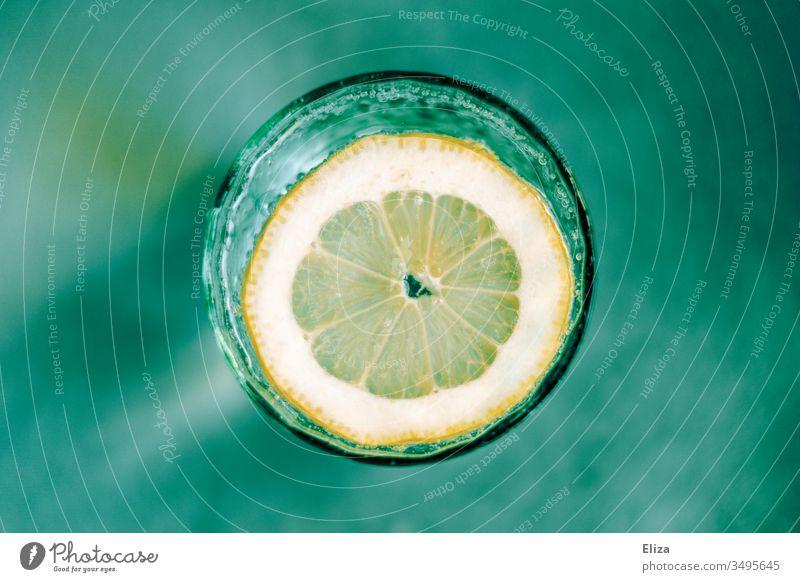 Ein Glas mit sprudeligem Wasser und einer Zitronenscheibe von oben auf türkisem grünen Hintergrund Wasserglas Sprudelig Unschärfe Vogelperspektive gelb frisch