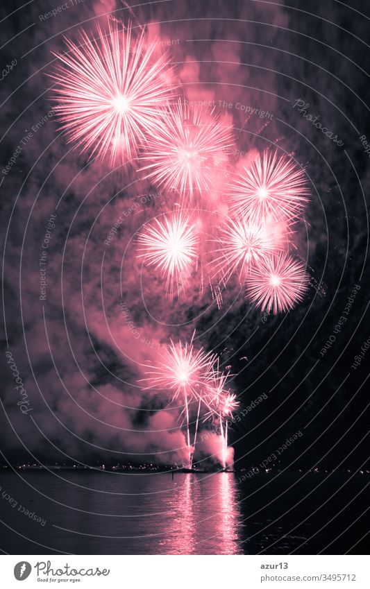 Luxus-Feuerwerksveranstaltung Himmel-Wasser-Meeresschau mit roten Sternen. Hochwertiges Unterhaltungs-Zaubersternfeuerwerk z.B. zu Silvester oder zur Feier des Unabhängigkeitstages. Schöne Spiegelungen auf der Seeoberfläche