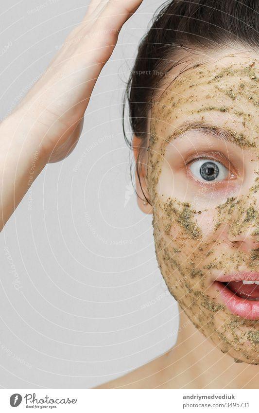 Hautpflege. Cosmetic Day. junges Mädchen in häuslicher Form, die Haare mit den Händen oben zusammengerafft. Mit ökologischer, pflanzlicher, natürlicher Maske, grün im Gesicht. Vorderansicht.