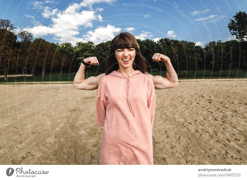 Sportlich-energetische athletische Frau trägt ein rosa Sporthöschen, das ihren Bizeps zeigt, sie mag Sport und einen aktiven Lebensstil. Athlet Muskel Fitness