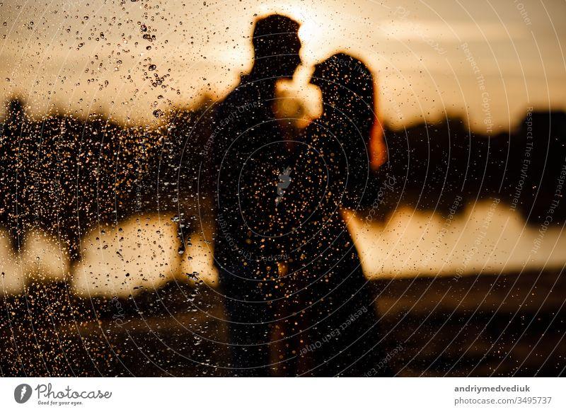 Silhouette eines liebenden Paares, das sich bei Sonnenuntergang auf dem See umarmt. Schönes verliebtes junges Paar, das bei Sonnenuntergang in den Strahlen des hellen Lichts am Ufer des Sees spazieren geht. copy space. selective focus